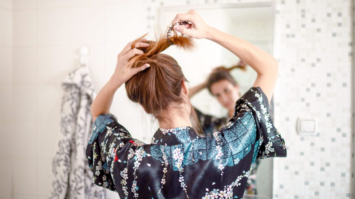 woman tying hair up