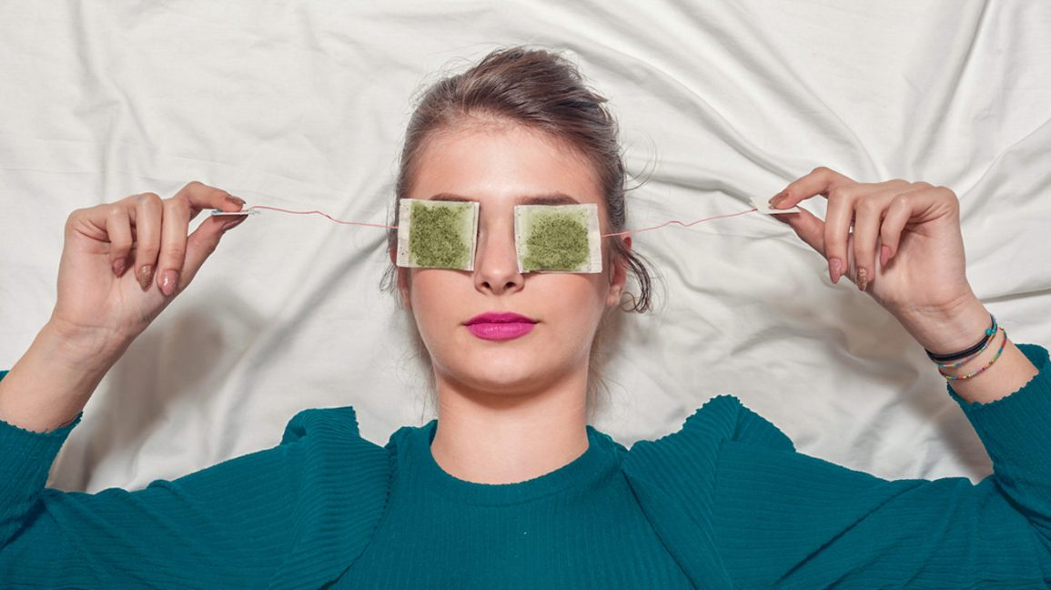 A woman lying on her back with green tea bags on her eyes.