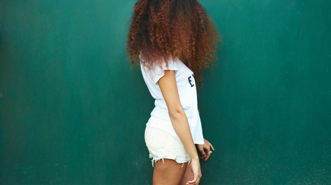 A profile of a woman with thick curly red-brown hair, wearing a t-shirt and shorts, standing against a teal-green background.