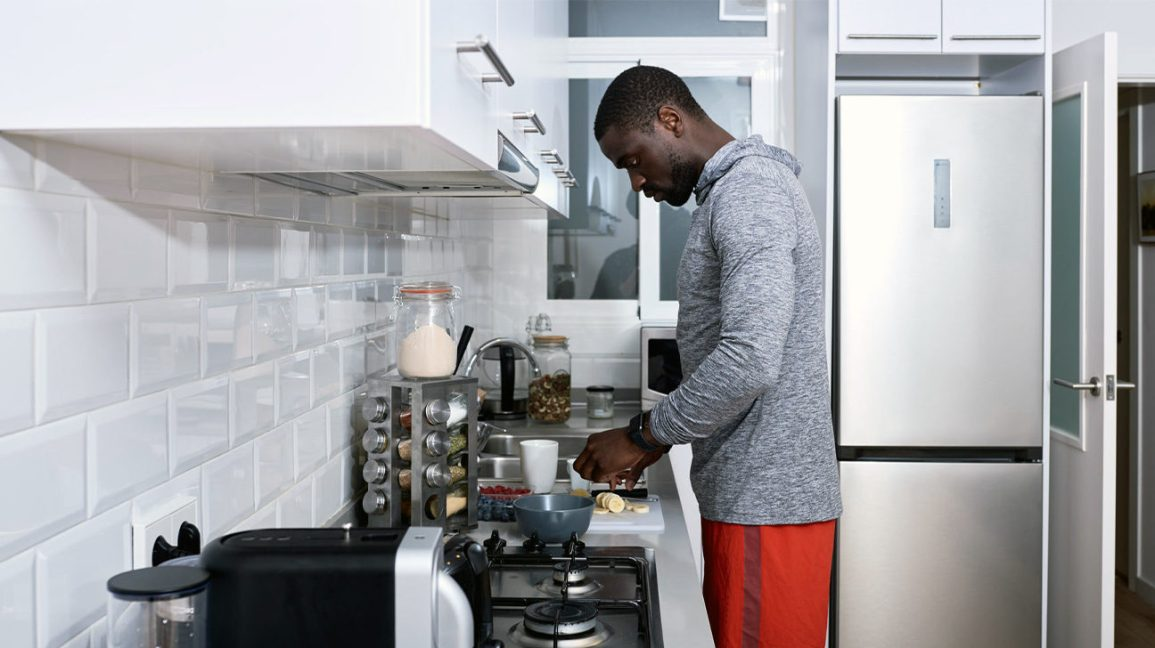 Athletic man preparing food in kitchen