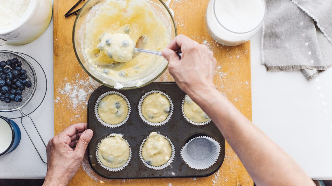 Someone filling blueberry muffin dough into muffin tins