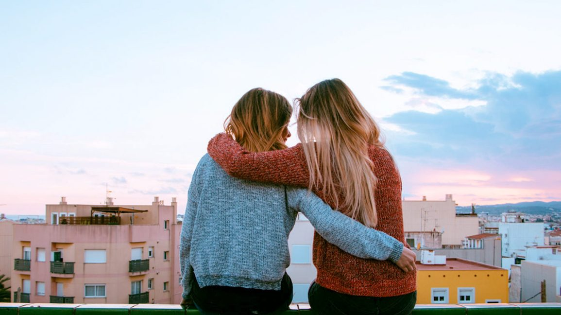 two friends sitting on a rooftop railing, holding each other and looking out at the skyline