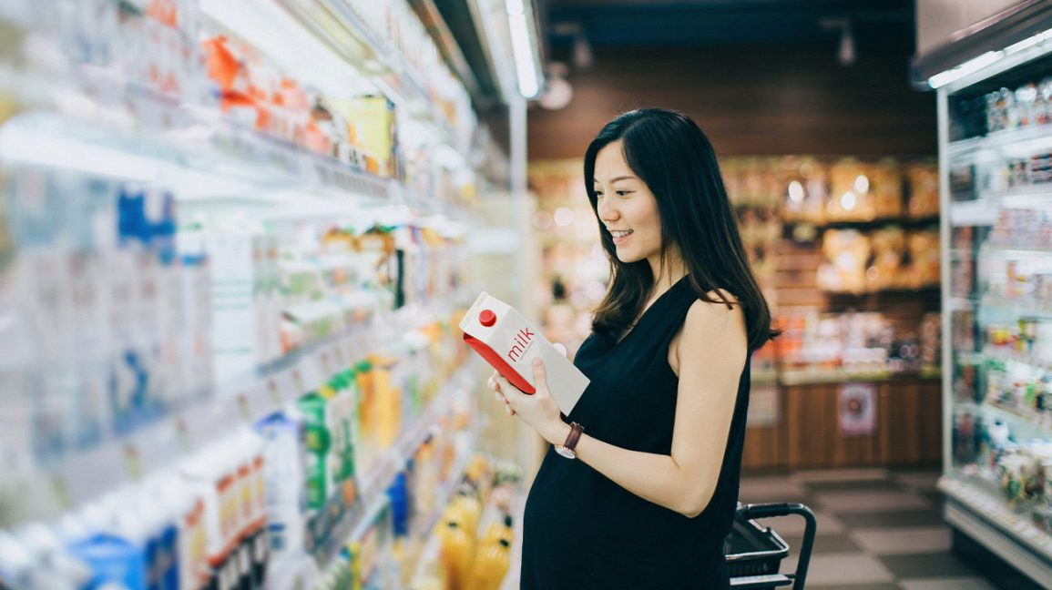 Asian pregnant women shopping for milk