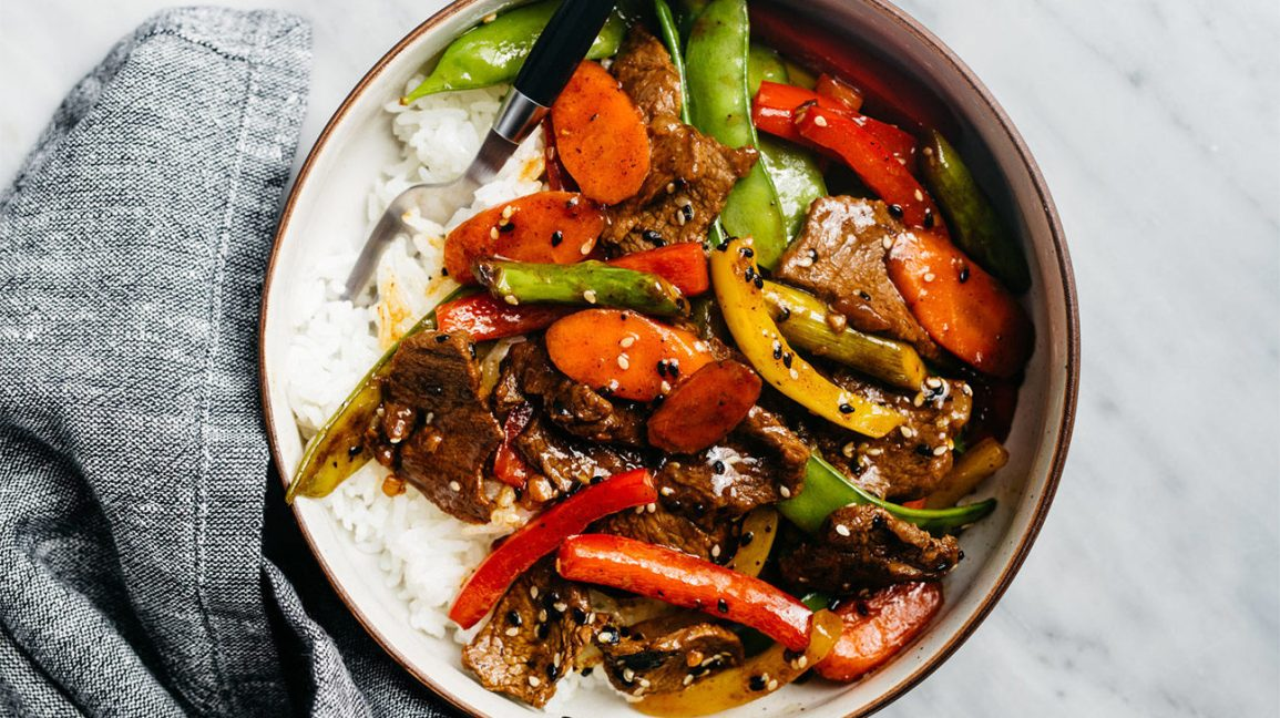 A vertical-diet-friendly bowl of rice with steak, bell peppers, carrots, and sugar snap peas