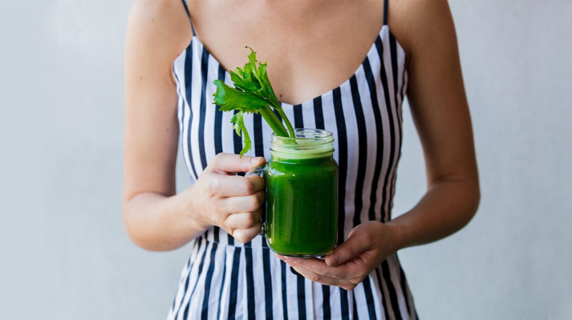 Woman holding celery juice smoothie