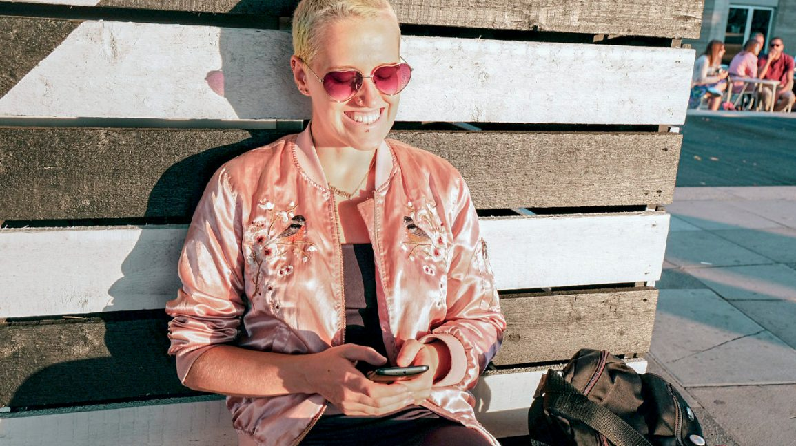 person in pink heart-shaped sunglasses and a pink jacket sitting on a bench texting