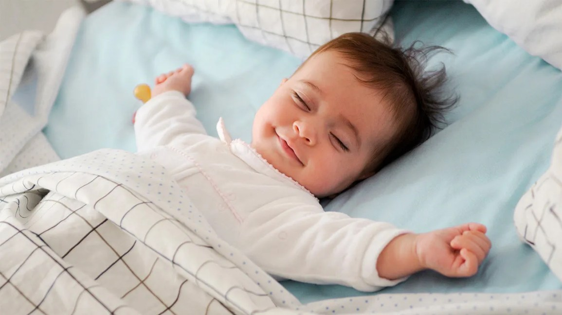 A baby sleeping happily using white noise.