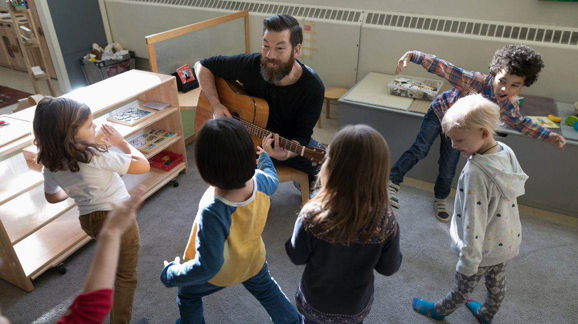 teacher playing an acoustic guitar for a group of elementary school students