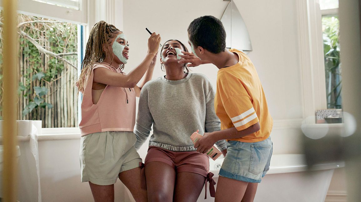 a group of friends helping each other apply clay face masks in the bathroom