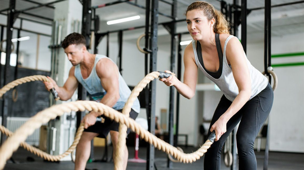 two people using battle ropes at the gym