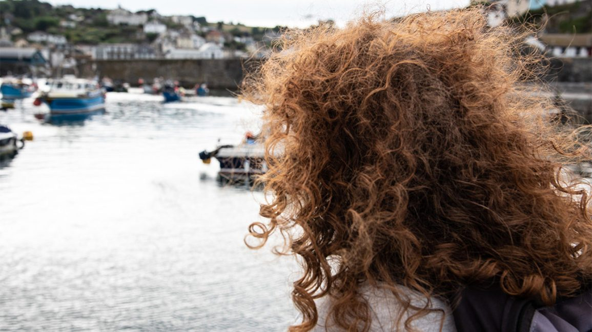 A woman with coarse, curly hair looking out over the water.