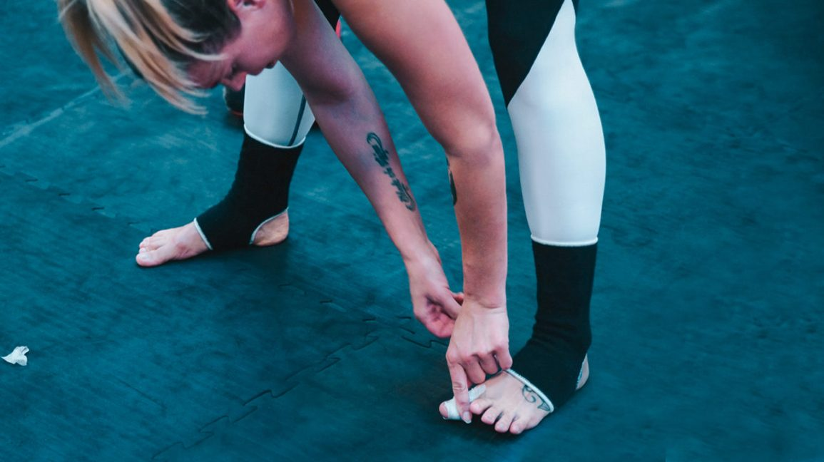 A woman in workout gear and bare feet, bending over to scratch an itch between her toes.