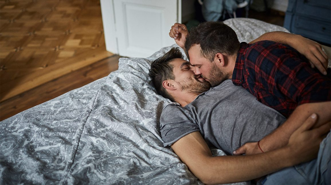 gay couple cuddling and kissing in bed