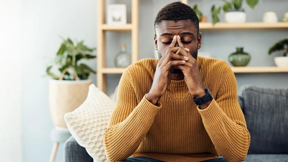 Um homem sentado em um sofá na sala de estar, com os olhos fechados, os dedos entrelaçados sobre o nariz, possivelmente por sentir que vai desmaiar.