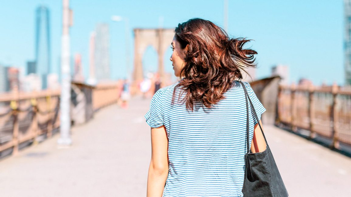 back view of person walking along the Brooklyn Bridge in New York