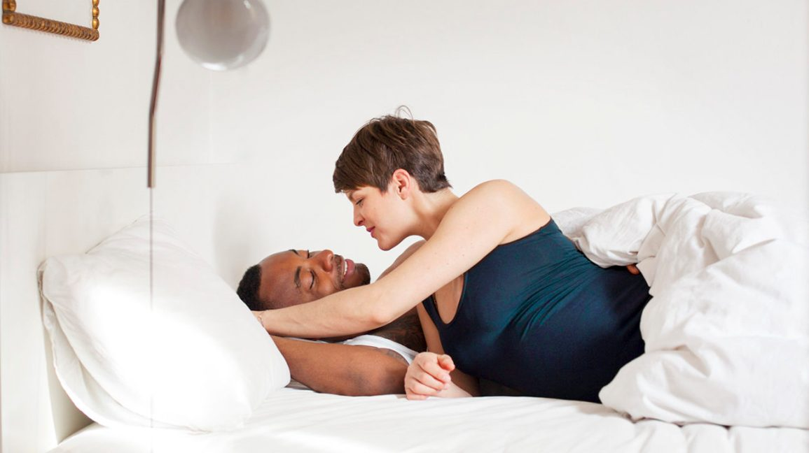 Pregnant woman and male partner in bed together