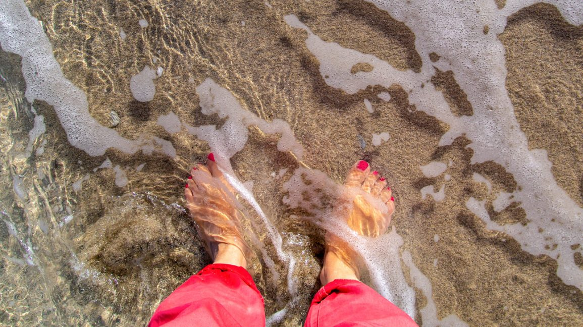 A view taken from above of a person's lower legs and feet, standing in shallow sea water.