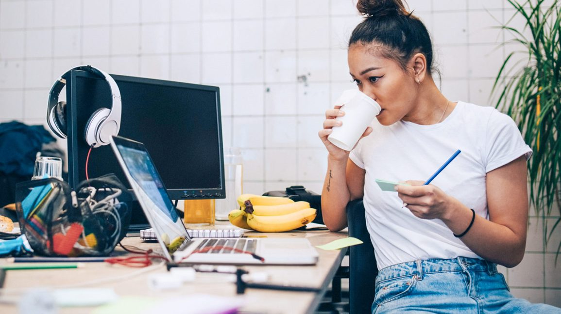 A woman sitting at a cluttered desk trying to stay focused on her computer while drinking coffee.