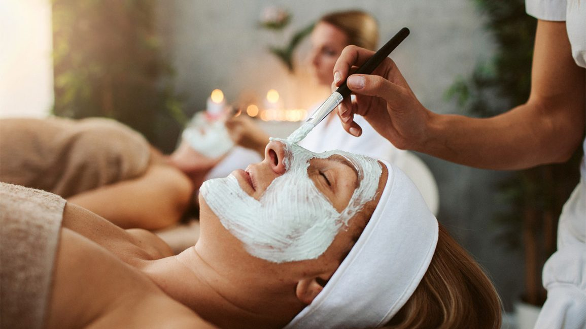 person laying down on a spa bed with their eyes closed while an esthetician applies a face mask