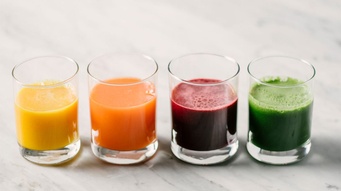 Four glasses with different juices