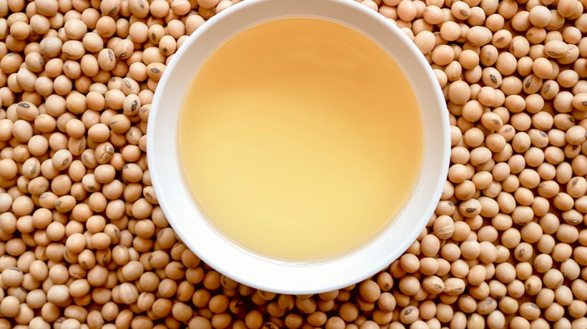A bowl of soybean oil in a bed of soybeans