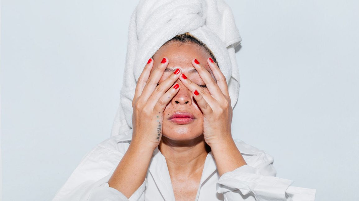 person in a white rob with a white towel wrapped around their hair, covering their face with their hands