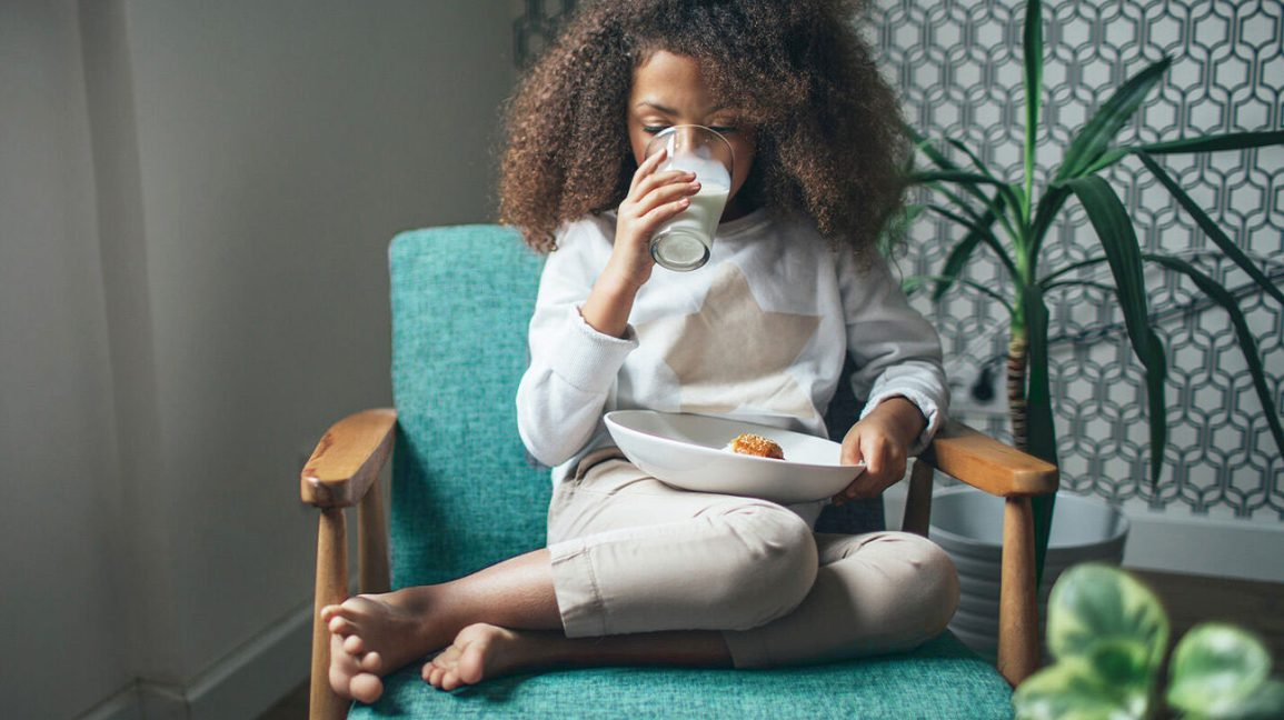 Young girl having a snack and drinking milk