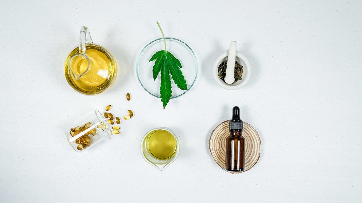 a bottle of oil, a cannabis leaf, oil capsules, and cbd oil