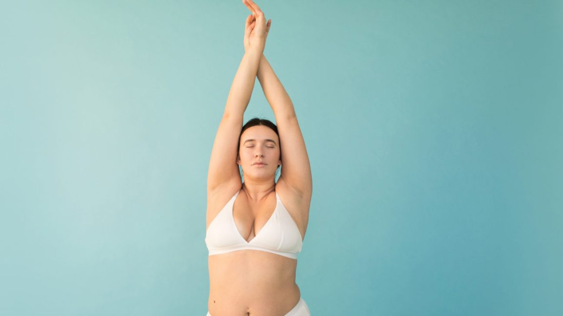 plus-size model wearing white undergarments with arms raised overhead against a light blue background