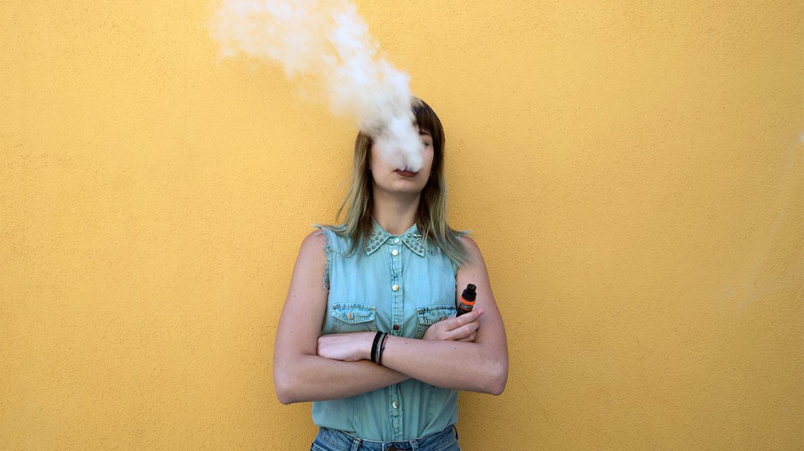 A young woman blowing smoke into the air from an electronic cigarette that likely contains nicotine.