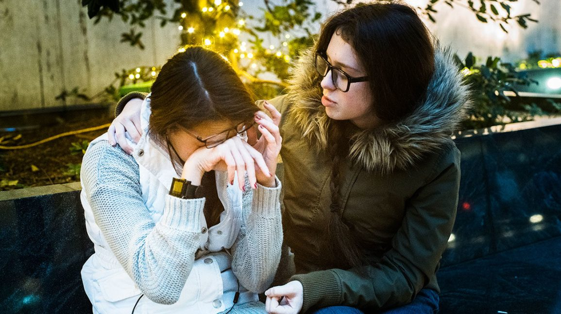 woman sitting outside with crying friend who she's comforting
