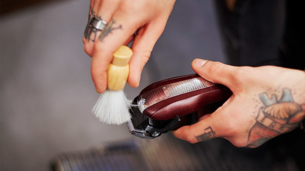 hand holding a brush and cleaning an electric razor
