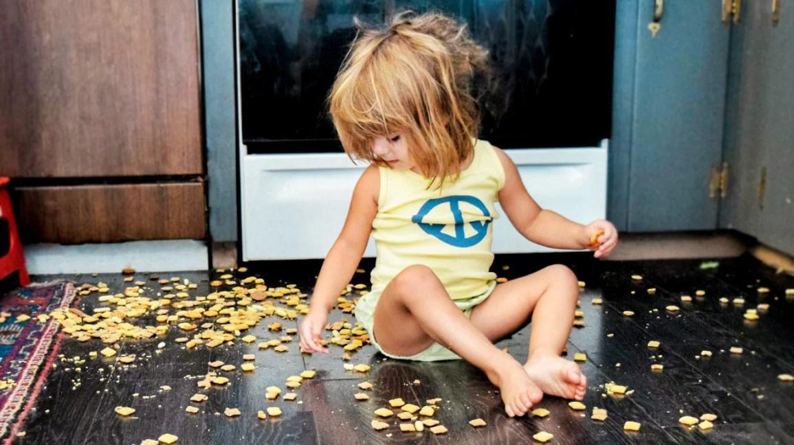 Un bambino seduto sul pavimento con i cracker sparsi per terra.