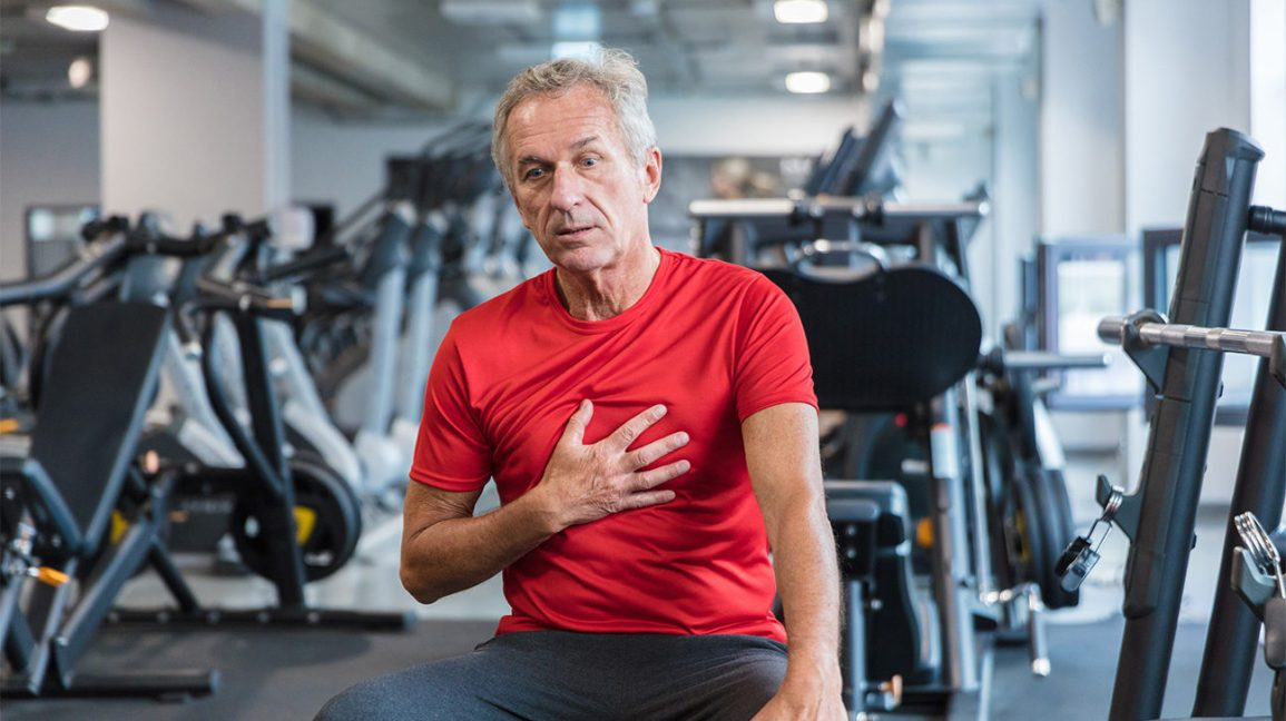 A man sitting in a gym, holding his chest due to possible chest and shoulder pain.