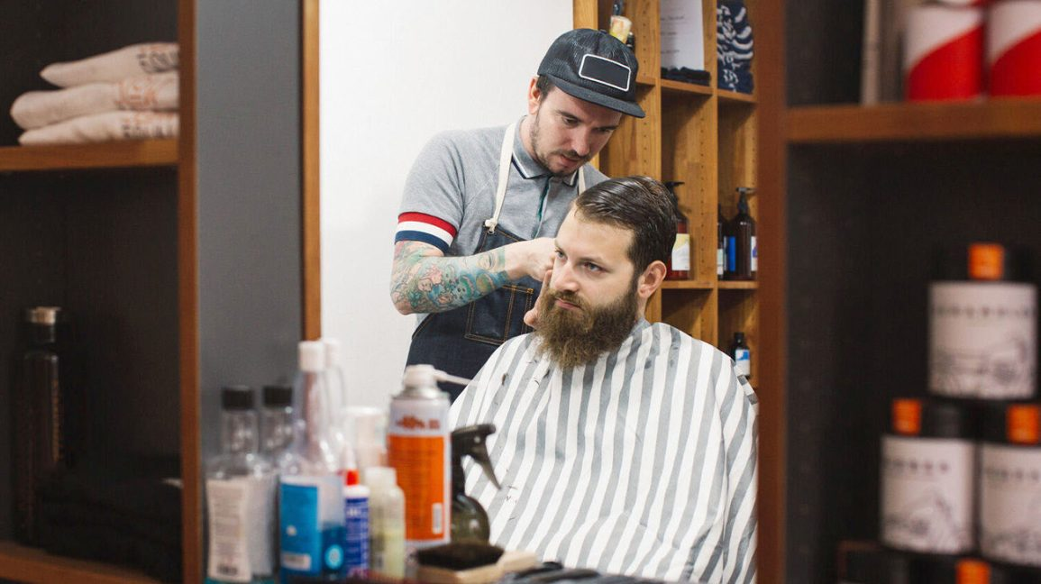 man with beard getting his hair cut by a tattooed barber