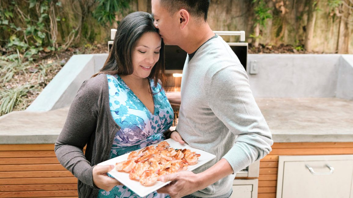 Man kissing forehead of expectant mother holding plate of shrimp