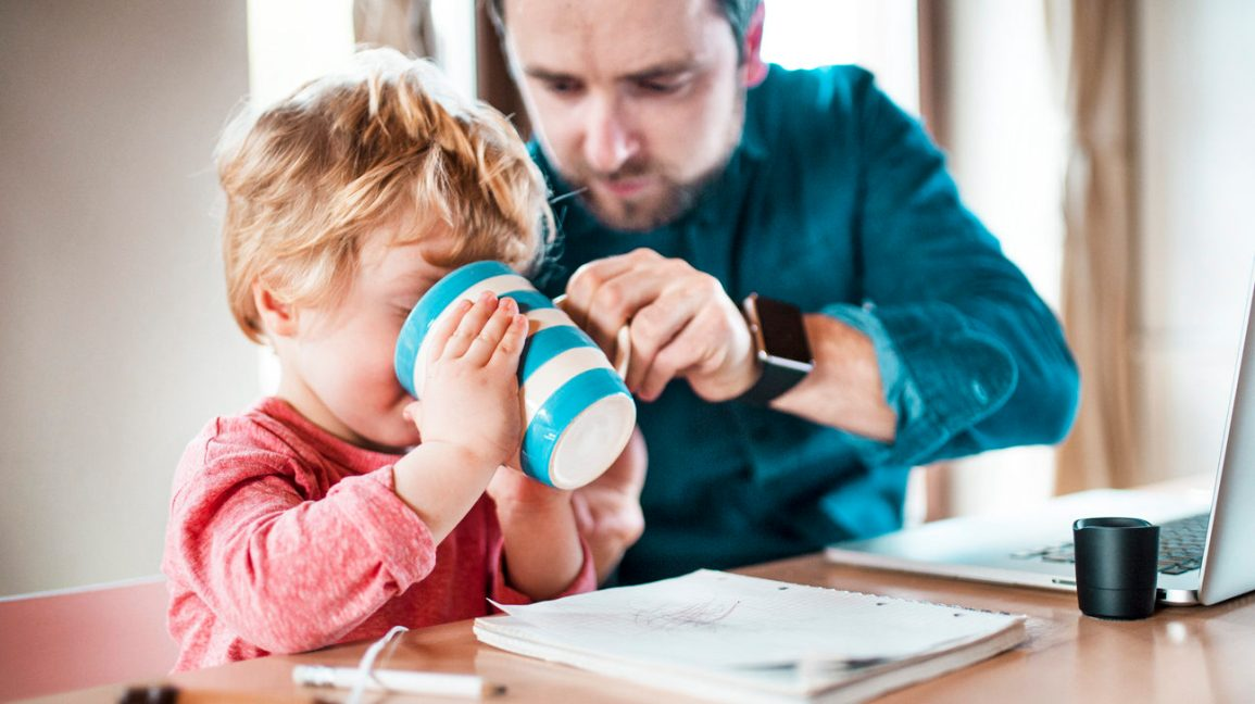 toddler drinking out of cup beside dad