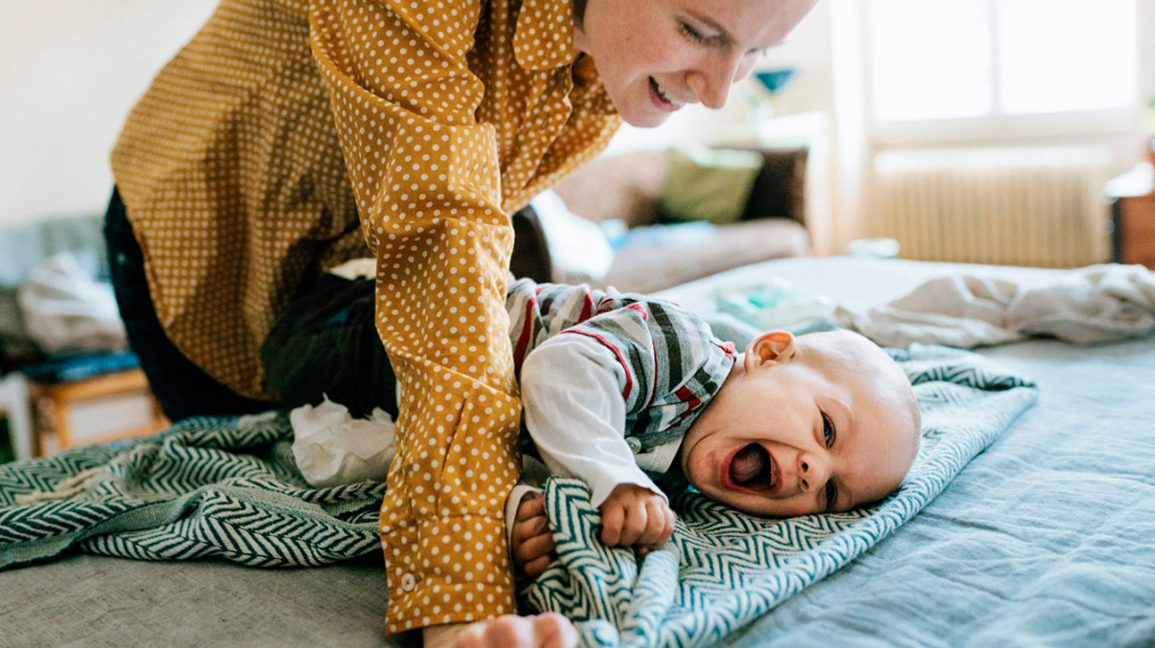 caregiver plays with smiling baby