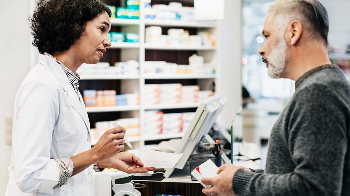 A pharmacist providing advice to a male customer about antibiotics and diarrhea.