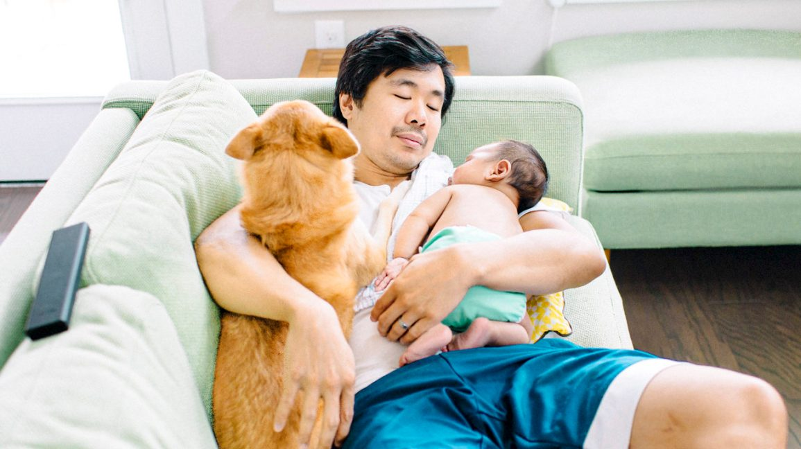 man cuddles on the couch with a dog and a baby