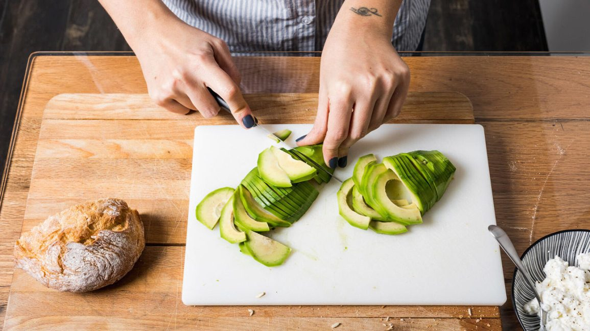 slicing avocado on a cutting board