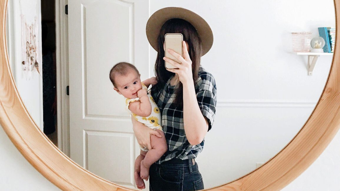 woman holding baby takes mirror selfie