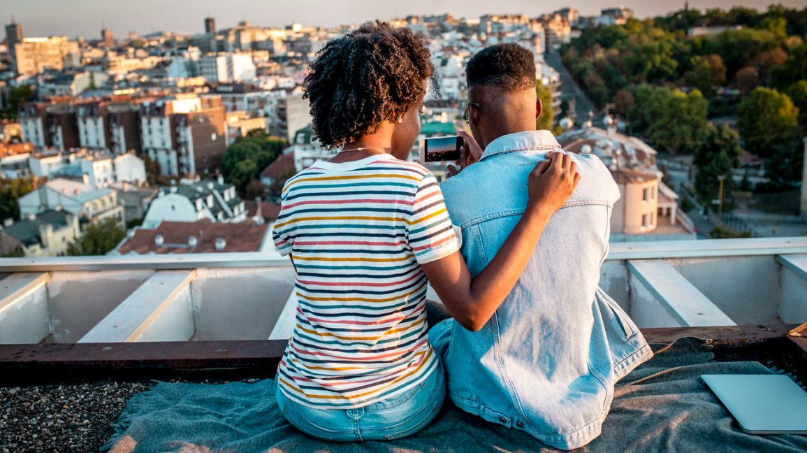 view of a couple sitting side-by side on a rooftop with their backs to the camera