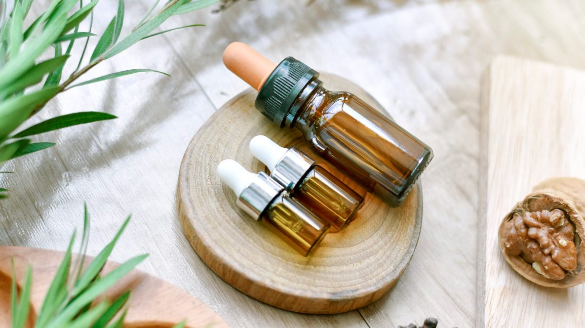 three essential oil dropper bottles on a piece of wood