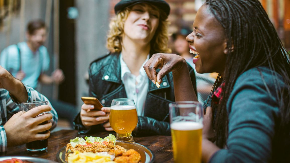two friends laushing while drinking beer and eating
