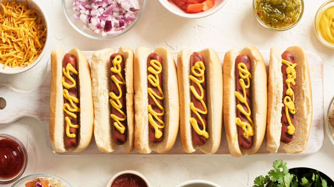 Six hot dogs on a table surrounded by condiments