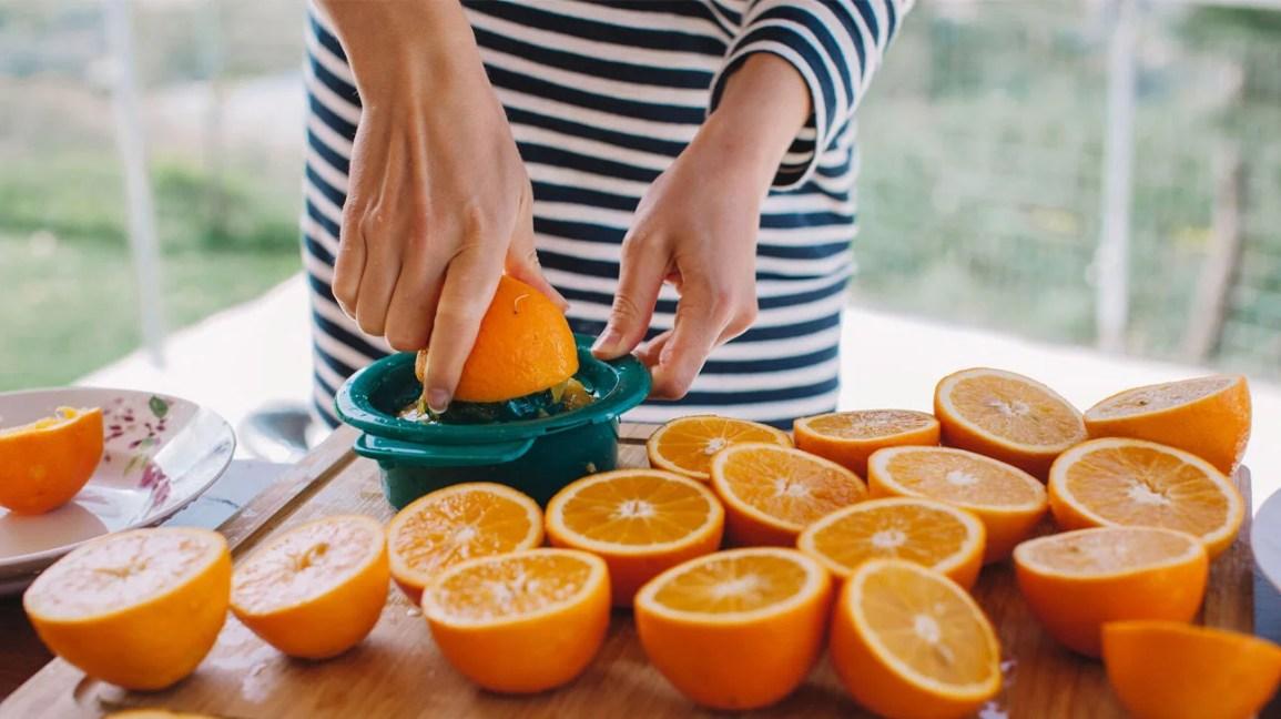 Mulher fazendo suco de laranja