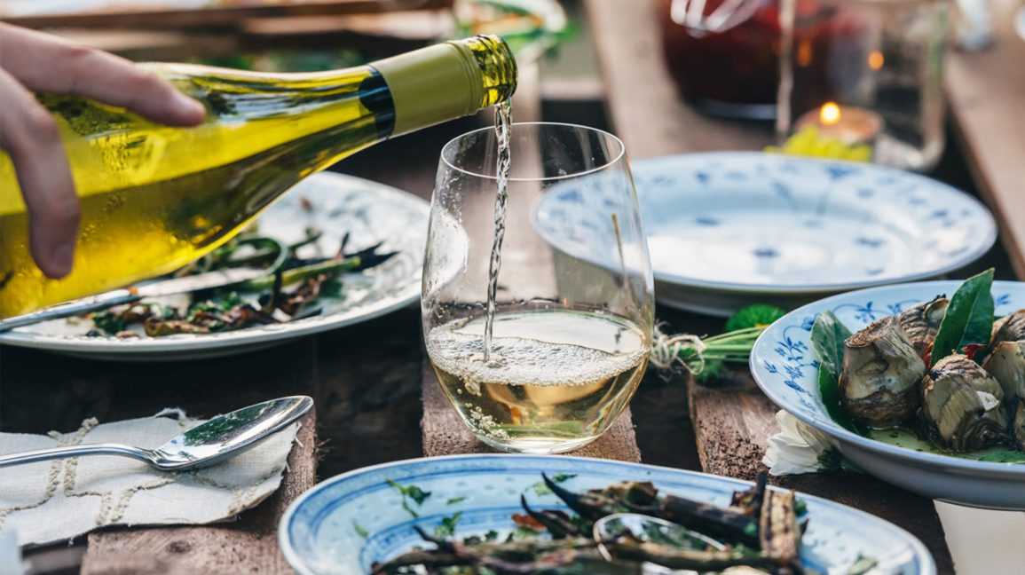 hand pouring white wine into glasses on a table with plates of food