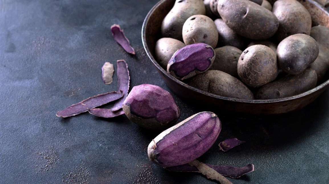 A bowl with purple potatoes and some peeled ones