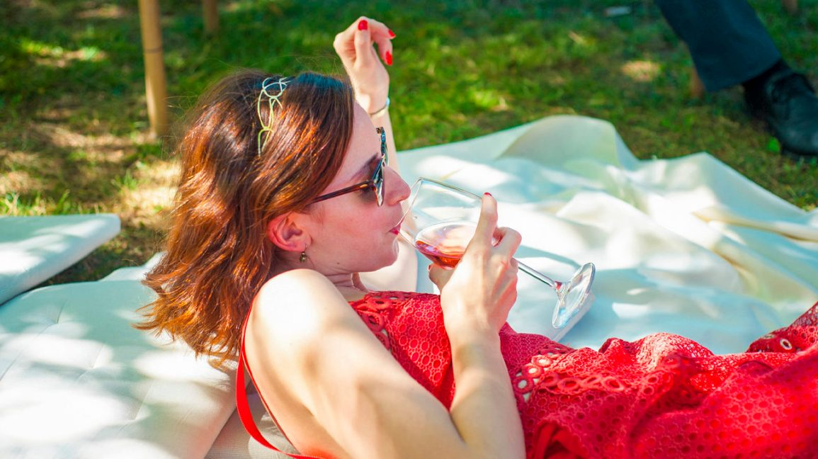 woman in red dress sipping wine on a picnic blanket